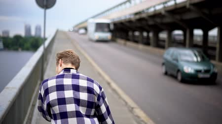 tcheco : Thoughtful Young Man Walking On Bridge Pavement. Cars On The Road. Man Alone Concept. Stock Footage