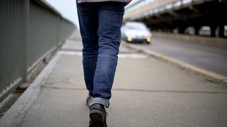 tcheco : Young Man Wearing Blue Jeans Walking On Bridge. Selective Focus On Legs. Man Alone Concept.