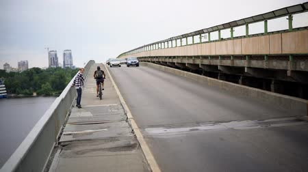 tcheco : Young Man Running After Bycicle Rider On Bridge Pavement. City Walking Concept.