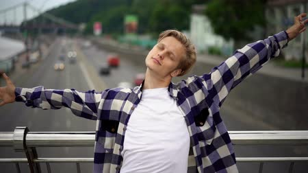 čeština : Front Footage Of Handsome Man In Casual Clothes Standing At Bridge Handrails. Solo Walking Concept.