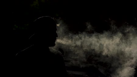 cigar : Silhouette Of Man Breathing Out Clouds Of Smoke. Slow Motion Of Young Vaper Smoking An Ecigarette Outside. Dark Background. Stock Footage