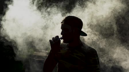cigar : Handsome Vaper Holds An Ecigarette In His Mouth While Standing In The Clouds Of Smoke. Silhouette Of Bearded Man Vaping And Making A Puff. Clouds Of White Smoke Swirling In The Dark And A Silhouette Of A Man