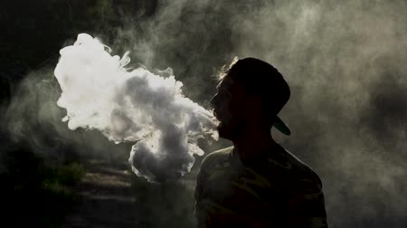 puffs : Young Man Standing In Puffs Of Smoke. Vaping Outside. Vaping Device Concept. Isolated On Smoke Background
