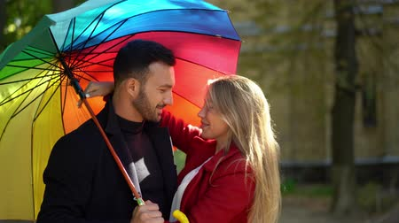 liefdevol : Charming Romantic Couple Standing Under Rainbow Umbrella. Close-up Of Beautiful Blonde Woman In Red Coat Hugging Her Stylish Boyfriend Who Holds A Rainbow Umbrella.
