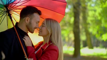 liefdevol : Close-up Of Lovely Couple Rubbing Noses While Standing Under Rainbow Umbrella. Slow Motion Of Attractive Woman Looking With Love At Her Handsome Husband. Under Rainbow Umbrella In The Park. Romance Concept