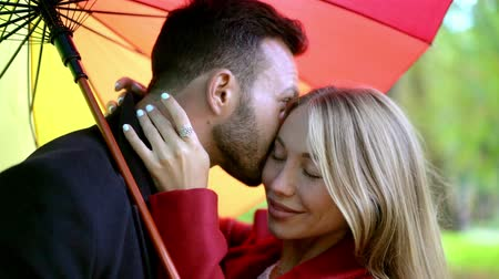 liefdevol : Smiling Young Woman Hugs Her Boyfriend Who Kisses Her Check And Holds A Rainbow Umbrella. Portrait Of Couple Gently Cuddling Under Rainbow Umbrella In Slow Motion.