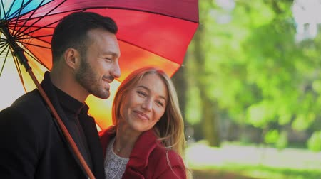liefdevol : Happy Couple Laughs Together While Standing Under Rainbow Umbrella In The Park. Close-up Of Smiling Stylish Man Holding Rainbow Umbrella And Laughing Beautiful Woman Hugging Her Boyfriend. Slow Motion Stockvideo
