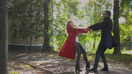casal : Happy Couple Holds Hands And Spins Around In The Park Under Bright Sunshine. Slow Motion Of Cheerful Man And Woman On Their Date Whirling In The Park. Stock Footage