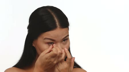 soczewki kontaktowe : Beautiful woman removes contact lens. Female on white background shows how to remove contact lens.