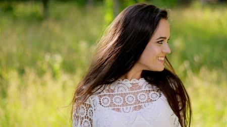 daha fazla : Brunette with an Attractive Smile in a Romantic Style in the Garden. Long Hair and a Gentle White Dress Make Her More Tender. Close Up Shot. Stok Video