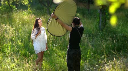 reflektör : Photographer Uses A Circular Reflector To Brighten The Model s Face During The Outdoor Photoshoot. Slow Motion Of Charming Girl In White Dress Touching Her Long Dark Hair And Posing While Her Face Is Being Brighten Up By The Reflector.