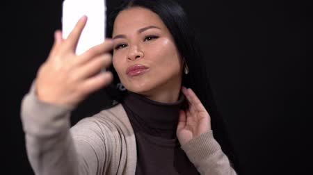 pocałunek : Beautiful Asian Poses To Do Great Selfie On The Smartphone Camera. Smiling Woman Winks And Sends A Kiss While Doing Selfie.
