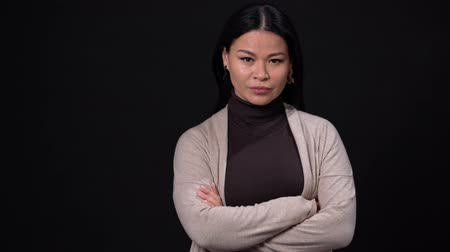 boring : Close Up Of Attractive Woman In Cardigan Holding Crossed Arms Over Black Background. Pretty Asian Crosses Her Arms While Looking Tense In The Camera. Stock Footage
