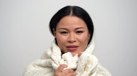 romance : Cute Brunette Woman with Narrow Eyes on a White Background. She is Wearing a White Knitted Scarf. She Gently Wraps Herself in a Scarf. Asian beauty concept. Close Up Shoot.