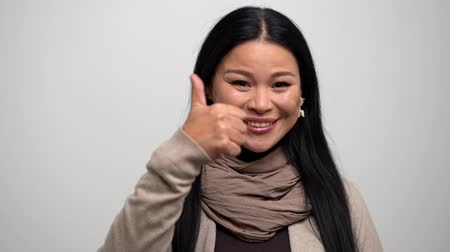 okey : Attractive Woman With Dark Hair Smiles And Shows Her Like With Thumb Up. Portrait Of Asian Female Gesturing An Ok Sign And Winks At Camera.