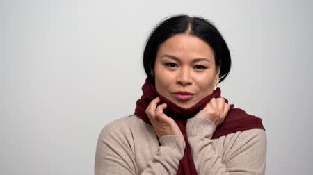 lenço : Beautiful Brunette Woman with Narrow Eyes on a White Background. The Red Scarf Warms Her from the Cold. She is Wearing a Brown Sweater and a Beige Cardigan. Asian beauty concept. Close Up Shoot.