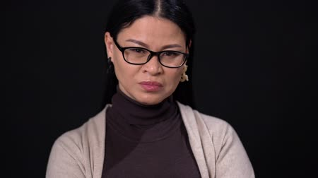 сомнение : Asian Businesswoman In Glasses And Casual Clothes. Looking Serious. Isolated On Dark Background. Стоковые видеозаписи