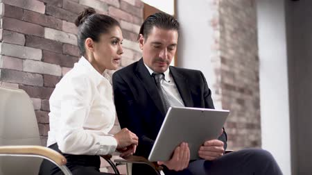 empregador : Man And Woman Sitting On Office Chairs And Discussing Data On Tablet. Weariung Office Clothes, Business Concept.