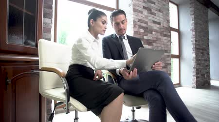 empregador : Beautiful Woman Showing Her Male Colleague Data On Tablet. Sitting On Chairs At Window. Business Concept. Stock Footage