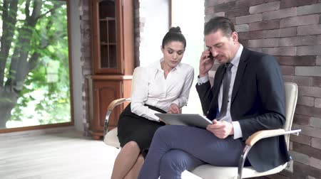 conference table : Managers of a Large Company a Man and a Woman Sit in a Room for Conversation. They are Planning a Meeting with Partners. A Man Conducts a Business Conversation on the Phone. Stock Footage