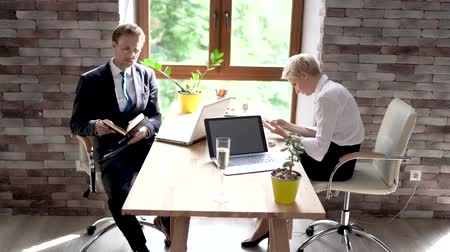 empregador : Man And Woman Sitting At Desk In Office. Man Making Notes While Woman Typing Message. Office Work Concept.