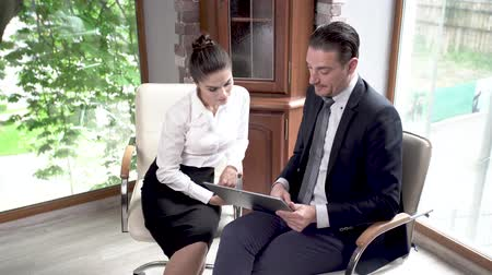 magyarázza : Elegant Businessman Explains Details To His Beautiful Colleague. Serious Businesswoman Carefully Listens To The Idea Of Her Coworker. Business Negotiation Concept