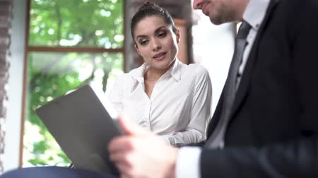 trabalhar fora : Concentrated Businesswoman Points Out Some Changes At The Tablet For Her Male Colleague. Blurred Image Of Male Hand Holding A Table The Foreground. Selective Shot. Low-Angle Shot Vídeos