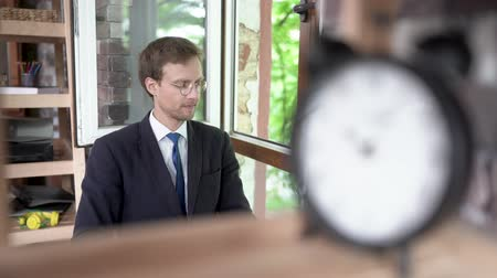 alarma : Calm Businessman In Glasses Is Sitting Still At The Table. Blurred Alarm Clock On The Foreground. Meditation In The Office Concept. Archivo de Video