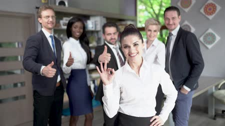 pulgar : Cheerful Brunette Businesswoman Stands In Front Of Her Happy Colleagues Showing Ok Sign. Blurred Coworkers On The Background Show Their Big Thumbs Up While Their Female Boss Shows Ok. Teamwork Concept