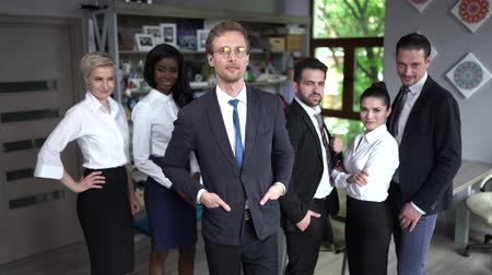 armen over elkaar : Handsome Boss In Glasses Holds His Hands In The Pockets Standing In Front Of His Employees. Serious Man In Glasses And A Suit Crosses His Hands Standing Among His Smiling Colleagues Stockvideo