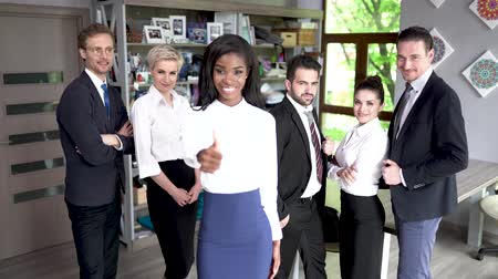 subordinate : Beautiful African-American Woman In A Suit Shows Big Thumb Up Standing In Front Of Her Colleague. Smiling African Businesswoman Stands Among Her Subordinates Showing Big Thumb Up.