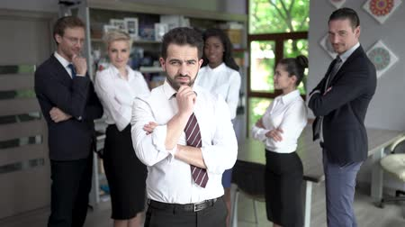 armen over elkaar : Concentrated Businessman Touches His Chin With One Hand While Standing In Front Of His Colleagues. Handsome Man In A Suit Shows An Ok Sign. Blurred Image Of Coworkers Standing On The Background.