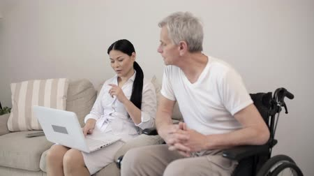 paraplegic : Senior Man In A Wheel Chair Tells His Doctor About His Problems. A Charming Nurse In A Lab Coat Sits At The Sofa Near Her Patient In An Armchair And Types His Complains On The Computer. Health Concept Stock Footage
