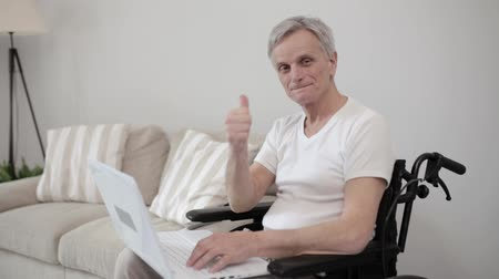 toegankelijkheid : Smiling Man In Casual Cloth In An Armchair Types On His Laptop. Happy Senior Man In A Wheel Chair Show An Ok Sign While Working At The Laptop. Big Thumb Up.