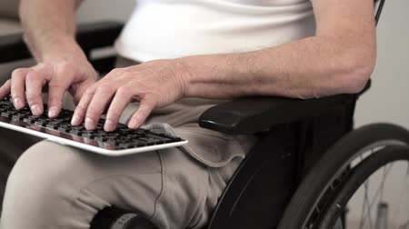paraplegic : Hands Of A Senior Man In A Wheel Chair Typing On A Keyboard. Dark Keyboard Is Laying On The Knees Of A Person In An Armchair While His Hands Type. Selective Shot. Close-Up. Disabled Person Concept