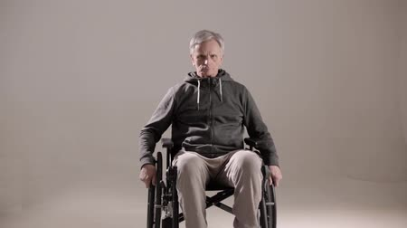 paraplegic : Frown Senior Man Rolls Closer At A Wheel Chair. Serious Looking Man In An Armchair Spins The Wheels Of His Chair Moving Towards Camera. Disability Concept. Studio Shot Stock Footage