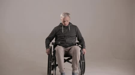 sérülés : A Gray Haired Man on a Wheelchair with An Evil look on a White Background. The Man is Wearing Sportswear and Hospital Slippers. Close Up Shot.