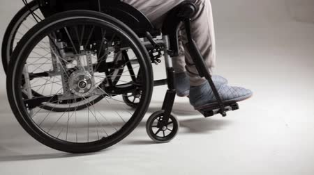 paraplegic : Doctor Moves A Wheelchair With A Patient. Legs Of A Disabled Person On An Armchair As Nurse Drives Him. Selective Shot. Close-Up Of Doctors And Disabled Persons Legs As Doctor Moving The Wheelchair.