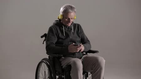 paraplegic : Satisfied Man In The Wheelchair Is Wearing A Big Yellow Headphone And Listening To Music. Smiling Disabled Man In An Armchair Moves His Head While Listening To Music In The Headphones. Happiness. Disability Concept Stock Footage