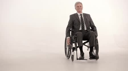 erişilebilirlik : Handsome Man In A Suit Is On A Wheel Chair Moving Around. Smiling Businessman In An Armchair Moves And Does Different Tricks. Charming Person In A Suit With Disability Moves On The Wheel Chair Feeling Good. Business Concept. Disability. Portrait. White St