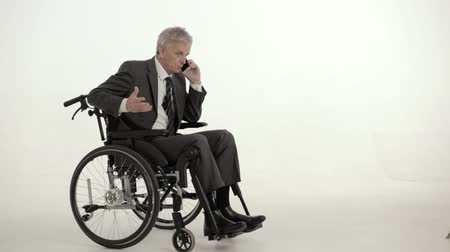 fauteuil : Busy Businessman In A Suit Sits In The Wheel Chair Talking On The Phone. Serious Man In A Suit Is Talking On The Phone Solving Work Issues While Sitting In The Armchair. Disability Concept. White Studio Background. Business