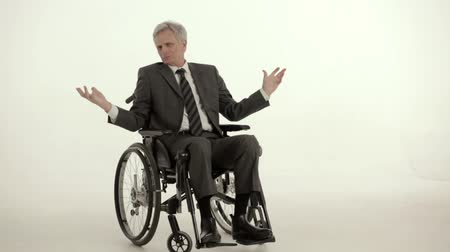 inválido : A Gray Haired Disabled Person in a Wheelchair Enjoys Life. The Man is Wearing a Suit. Despite the Disability a Man of Sound Mind and Full of Energy. Close Up Shot.