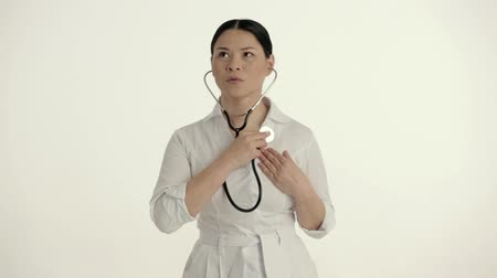 обеспокоенный : Concerned Woman In White Coat Holds A Stethoscope And Listens To Her Heartbeat. Worried Doctor With A Stethoscope Searches For The Heartbeat. Medical Concept. White Studio Background Стоковые видеозаписи