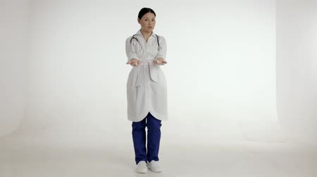 cortes : Charming Doctor With A Stethoscope Holds Two Test Tubes And Proposes To Take One. Polite Female Nurse Show To Tubes And Tells The Difference. Medical Concept. White Studio Background.