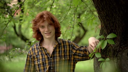 laboring : Young Boy with Red Hair in a Romantic Image in a Green Garden. The Guy Leaned Against the Tree and Smiles Sweetly. A Plaid Casual Shirt Compliments His Style. Slow Motion Footage. Close Up Shot.