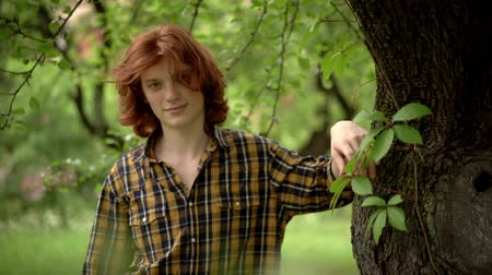 redhair : Attractive Boy In Checked Shirt With Red Hair Outside. Smiling Guy's Red-Hair Is Ruffled By The Wind. Slow Motion. Portrait