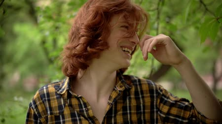 roodharige : Happy Young Guy in the Spring Garden. The Wind Develops His Thick Red Hair. His Smile Makes the Image Romantic. Slow Motion Footage. Close Up Shot. Stockvideo
