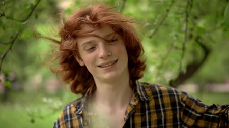 olhando para baixo : Lovely Red-Hair Guy Looks Down And Smiles. Wind Blowing The Handsome Smiling Guy's Ginger Hair. Slow Motion. Close-Up