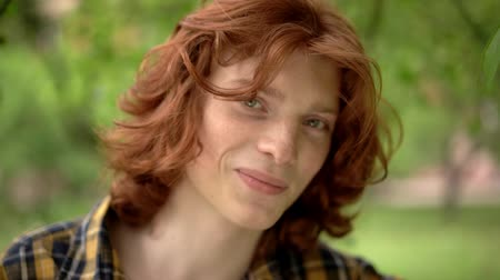 laboring : A Young Guy with Red Hair in a Green Garden. His Smile and Freckles on His Face Make the Image More Romantic. He is Wearing a Casual Plaid Shirt. Slow Motion Footage. Close Up Shot. Stock Footage