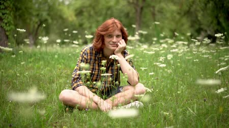 egyetlen virág : A Young Redhead Guy Sits on a Lawn in a Garden with Wildflowers. With His Hand He Props Up His Chin. There is a Smile on His Face. The Guy is Wearing a Casual Plaid Shirt and Denim Shorts. Slow Motion Footage. Close Up Shot. Stock mozgókép